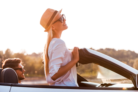 freedom woman: Enjoying the sun and fresh air. Side view of cheerful young woman leaning at the wind shield while her boyfriend sitting near on front seat of convertible