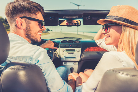 Enjoying their road trip. Side view of cheerful young couple holding hands and looking at each other while sitting inside of their convertible Stock Photo