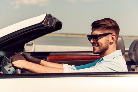Enjoying carefree ride. Side view of smiling young man looking forward while driving his white convertible