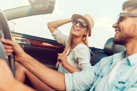 vitality: Having fun along the way. Beautiful young woman smiling and adjusting her hat while her boyfriend sitting near and driving convertible Stock Photo