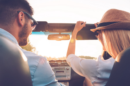 woman driving car: Enjoying road trip together. Rear view of joyful young couple having fun while riding in their convertible Stock Photo