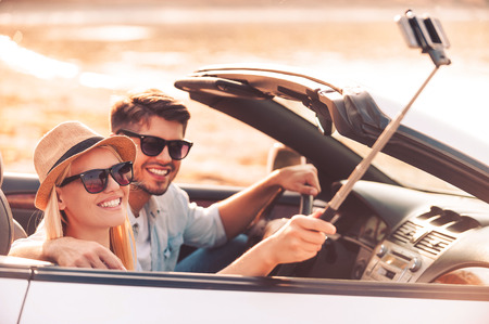 making love: Selfie to remember the day. Happy young couple using monopod while making selfie inside of their convertible