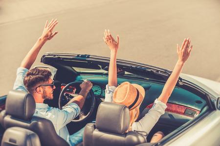 personas mirando: Alejarse de todo. Vista superior de la alegre joven pareja manteniendo los brazos en alto mientras viajaba en su convertible blanco