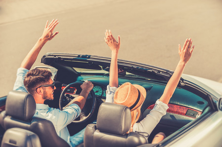 getting away from it all: Getting away from it all. Top view of cheerful young couple keeping arms raised while riding in their white convertible