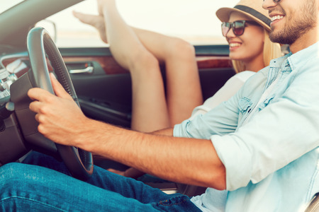 people relaxing: It is so good to get away out of the city. Happy young woman relaxing on the front seat while her boyfriend sitting near and driving convertible Stock Photo