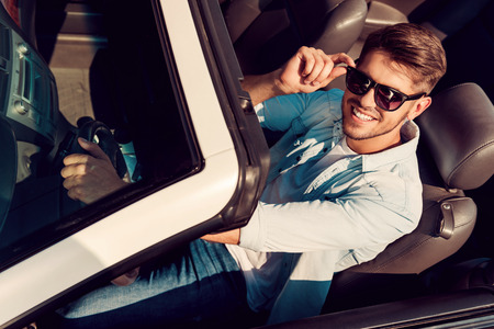 driving car: I love this car! Top view of handsome young man looking at camera and adjusting eyewear while driving his white convertible Stock Photo