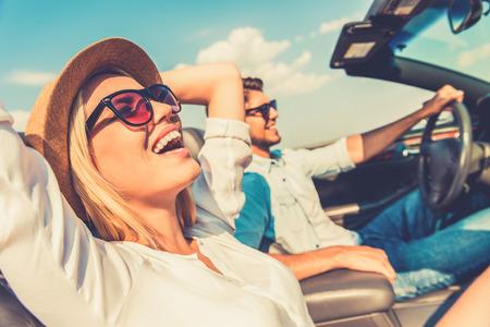 A liberdade da estrada aberta. Vista lateral da mulher alegre que relaxa no banco da frente, enquanto seu namorado sentando-se perto e dirigir seu conversível