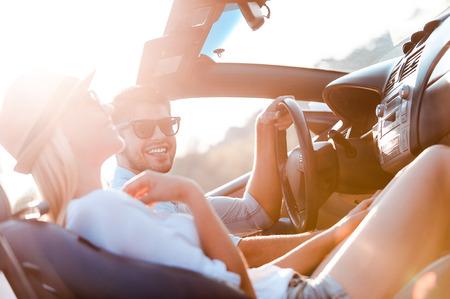 parejas felices: El mejor d�a para el viaje por carretera. Feliz pareja joven sonriendo mientras est� sentado en el interior de su convertible