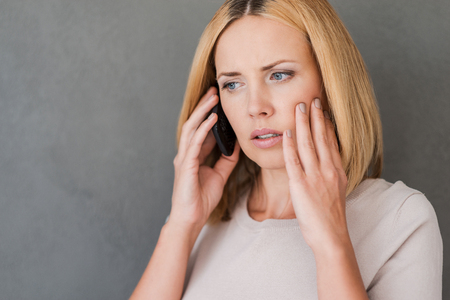 woman on phone: She just got bad news. Frustrated mature woman talking on the mobile phone and expressing negativity while standing against grey background Stock Photo