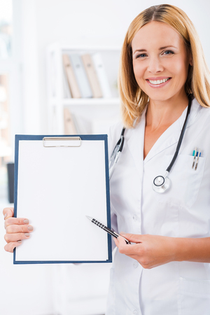 clipboard: Your test results right here. Happy female doctor in white uniform looking at camera and smiling while pointing at clipboard