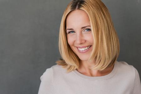 wunderschön: Zuversichtlich und schön. Schöne fällige Frau, die Kamera und lächelnd im Stehen vor grauem Hintergrund Lizenzfreie Bilder