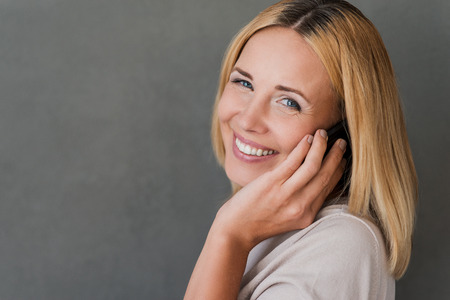 one woman: Nice talk with friend. Cheerful mature woman talking on the mobile phone and smiling while standing against grey background