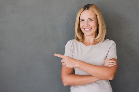 woman pointing: Reliable smile for your advertisement. Happy mature woman pointing away and smiling while standing against grey background