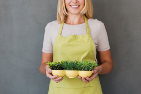more mature: Gardening is more than hobby. Cropped image of cheerful mature woman in green apron holding flower pot and smiling while standing against grey background Stock Photo