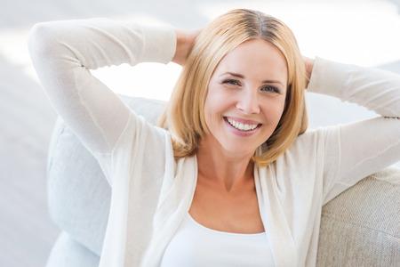 가장 편안한 장소 찾기. 손에 머리를 들고 소파에 앉아있는 동안 카메라를보고 웃는 성숙한 여자의 상위 뷰