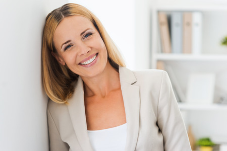 job satisfaction: Face of job satisfaction. Beautiful mature businesswoman looking at camera and smiling while leaning at the wall