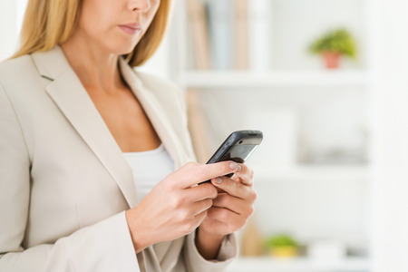 mobile business: Typing business message. Cropped image of mature businesswoman holding mobile phone while standing in office Stock Photo