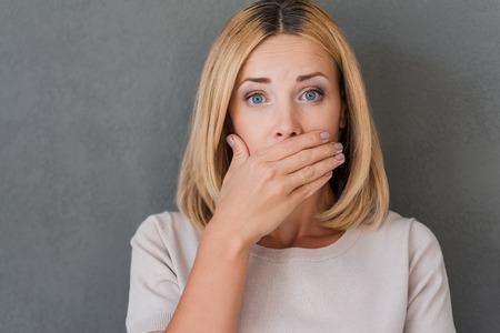 衝撃的なニュース。驚きの成熟した女性の手で口を覆っていると灰色の背景に対して立ったままカメラを見つめて