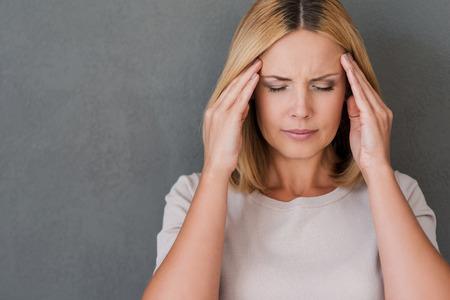 depresión: Necesito algunos analgésicos. Mujer madura deprimida tocar la frente y los ojos manteniendo cerrados mientras está de pie contra el fondo gris