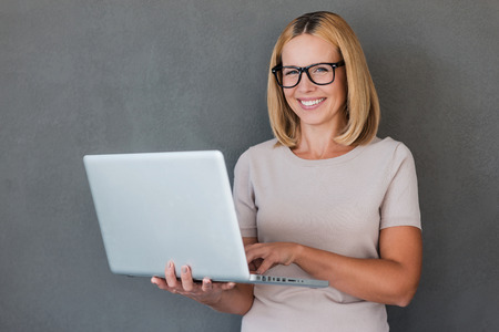 looking at computer: Smart beauty. Smiling mature woman holding laptop and looking at camera while standing against grey background Stock Photo