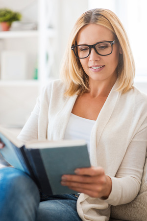 beautiful mature woman: Reading her favorite book. Beautiful mature woman in eyewear reading book while sitting on the couch Stock Photo