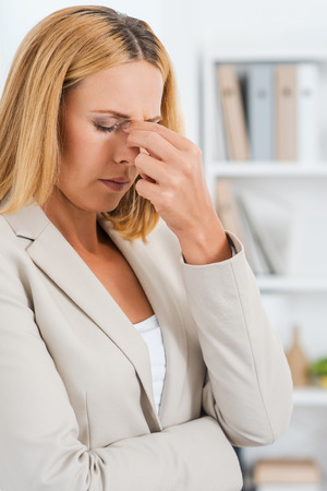 tired worker: How will I get through this day? Depressed mature businesswoman touching her nose and keeping eyes closed Stock Photo