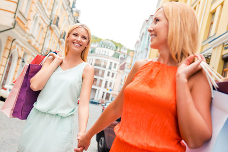 holding hands while walking: Spending great time together. Happy young woman and her mother carrying shopping bags and holding hands while walking along the street Stock Photo