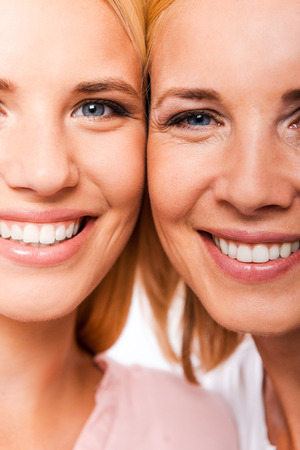 cheek: Daughter with mother. Close-up of mother and her daughter smiling and looking at camera while standing cheek to cheek against white background