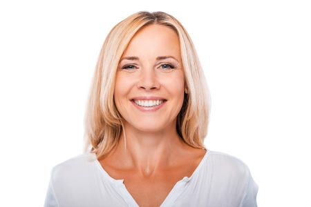 陽気な中年の女性。カメラ目線と白い背景に対して立っている笑顔幸せの成熟した女性の肖像画