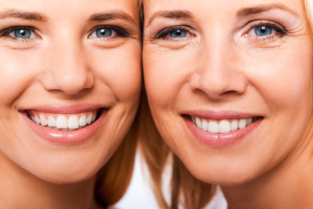 pretty face: Like mother like daughter. Close-up of mother and her daughter smiling and looking at camera while standing cheek to cheek against white background