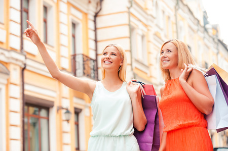 adult offspring: We have to visit this shop. Low angle view of cheerful young woman and her mother carrying shopping bags and looking away while walking outdoors