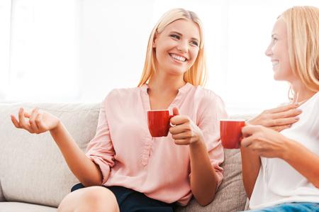 person sitting: Disfrutando de buen tiempo con la madre. Feliz mujer joven y su madre beber caf� y hablar mientras se est� sentado en el sof� junto
