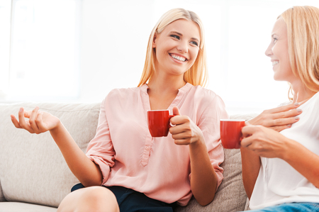 Enjoying good time with mother. Happy young woman and her mother drinking coffee and talking while sitting on sofa together Stock Photo