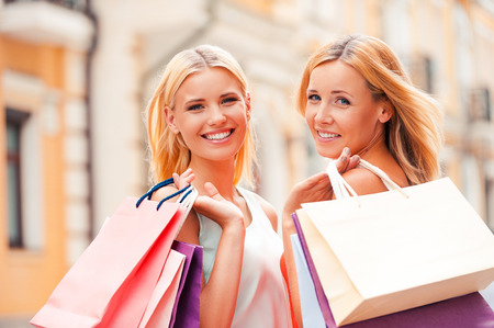 go shopping: We always go shopping together. Cheerful mature woman and her daughter carrying shopping bags and looking at camera while walking outdoors Stock Photo