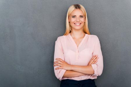 femmes souriantes: Confiant beauté et pure. Belle jeune femme regardant la caméra et de garder les bras croisés en se tenant debout sur fond gris