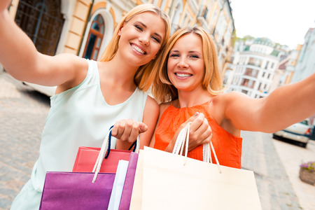 making love: We love selfie! Happy mother and her daughter making selfie on camera and holding shopping bags while standing outdoors Stock Photo