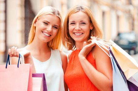 best friends: Mother and daughter are the best friends. Beautiful mature woman and her blond hair daughter holding shopping bags and looking at camera while standing outdoors