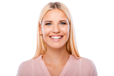 Ze kreeg mooie glimlach. Portret van vrolijke jonge vrouw op zoek naar de camera en glimlachen terwijl staande tegen een witte achtergrond