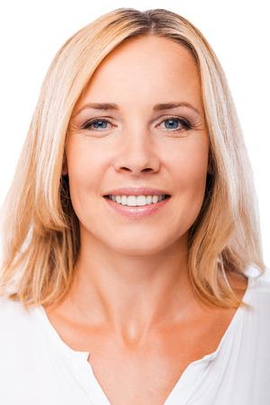 成熟した美しさ。カメラ目線と白い背景に対して立っている笑顔幸せの成熟した女性の肖像画