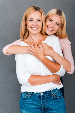 bonds: Family bonds. Smiling young woman embracing her mother while both standing against grey background