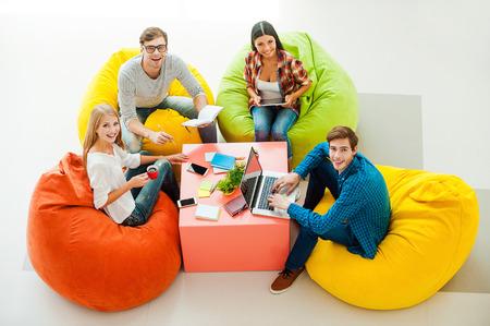 창조적 인 작업 공간. 다채로운 콩 가방에 앉아있는 동안 함께 작업하고 찾고 네 쾌활한 젊은 사람들의 상위 뷰 스톡 콘텐츠