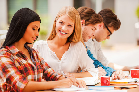 business education: Finding inspiration in friends. Happy young woman smiling and looking at camera while sitting with her friends at the wooden desk outdoors