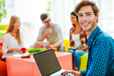 casual office: He is confident about his work. Smiling young man working on laptop and looking at camera while his colleagues working in the background