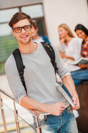 university life: University life is great! Smiling young man holding laptop and looking at camera while his friends standing in the background