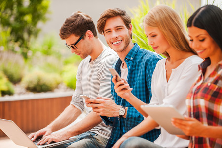 Living a digital life. Group of young people holding different digital devices while man looking at camera and holding mobile phone Stock Photo - 43053101