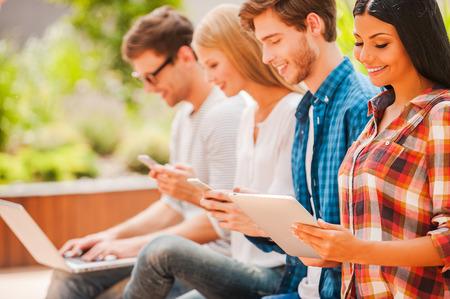 人: 數碼世界。快樂的年輕人集團持有不同的數字設備和微笑坐在一排,而戶外