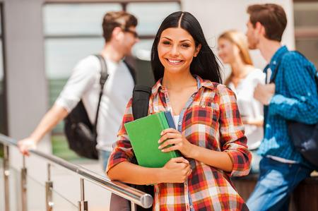 escuela edificio: Ella nunca se salta ninguna clase. Mujer joven feliz celebración de libros y mirando a la cámara mientras sus amigos de pie en el fondo