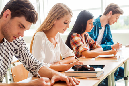 successful student: Concentrated on exam. Group of young students writing something in their note pads while sitting in a row at their desks Stock Photo