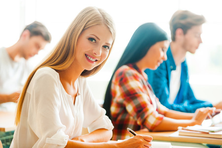 onderwijs: Hard werken voor goede cijfers. Mooie jonge vrouw schrijven en kijken naar de camera, terwijl haar klasgenoten studeren op de achtergrond