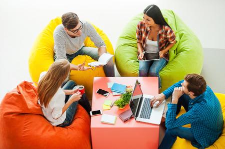 pessoas: Lugar onde as idéias nascido. Vista de cima de quatro jovens que trabalham junto ao sentar-se nas coloridas sacos de feijão